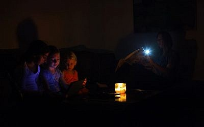 An Israeli family sits in the darkness of their home during a power outage, near the Israeli town of Netanya, on October 26, 2015. (Chen Leopold/FLASH90)