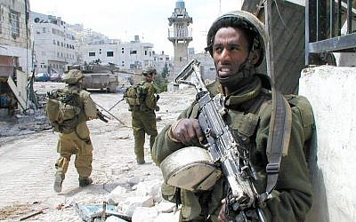 An IDF soldier stands guard in Nablus during Operational Defensive Shield in 2002. (IDF Spokeserson's Unit/Flickr)
