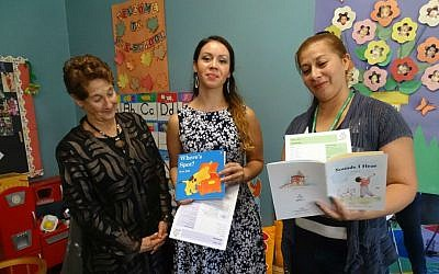 From left, Linda Frank, chair of HIPPY USA's trustees, and home visitors Sonia Sorto and Idis Argueta displaying some of the books and matching curricula given free to families in the HIPPY program. (Suzanne Pollak/via JTA)