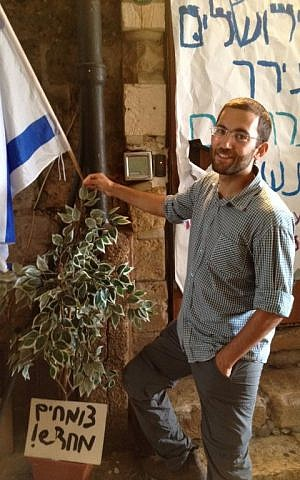 Youth organizer Yair Dan stands next to a tree sapling at the protest tent, with a sign reading 'growing anew,' October 8, 2015 (Elhanan Miller/Times of Israel)
