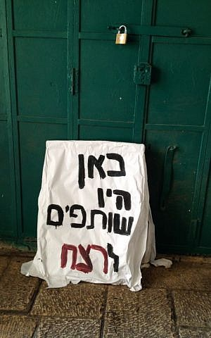 A sign reading 'here were accomplices to the murder,' lies against the shuttered door of a Palestinian shop on Hagai street, October 8, 2015 (Elhanan Miller/Times of Israel)