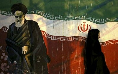 In this November 2, 2013 file photo, a veiled Iranian woman walks past a mural depicting the late revolutionary founder Ayatollah Khomeini, and national Iranian flag, painted on the wall of the former U.S. Embassy, in Tehran, Iran. (AP/Ebrahim Noroozi)