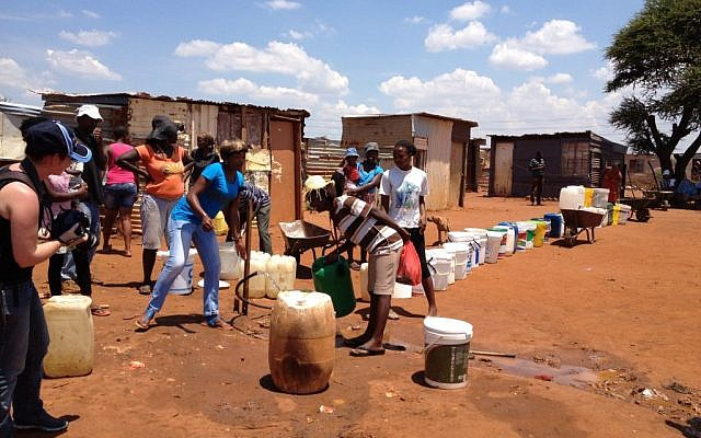 People lining up for water in an informal settlement outside of Johannesburg, South Africa (Courtesy)