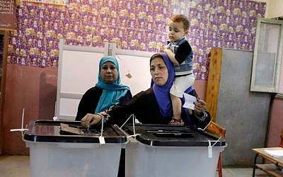 An Egyptian voter casts her vote at polling station during the first round of parliamentary elections, in Giza, Cairo, Egypt, Sunday, Oct. 18, 2015. (AP Photo/Amr Nabil)