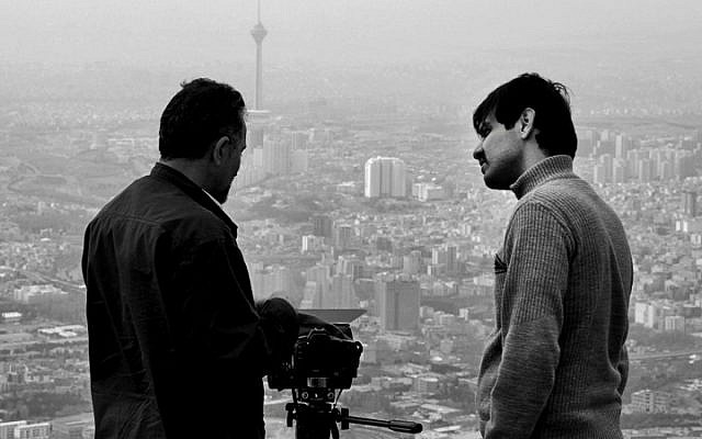 "In this undated photo provided by Iranian filmmaker Keywan Karimi, cameraman Arasto Givi, right, speaks with Karimi during a scene of the film ""Writing On The City,"" overlooking Tehran, Iran. In October 2015, a court sentenced award-winning Iranian filmmaker Karimi to six years in prison and to 223 lashes over his films, which authorities charged with ""insulting sanctities."" (Iranian filmmaker Keywan Karimi via AP)"
