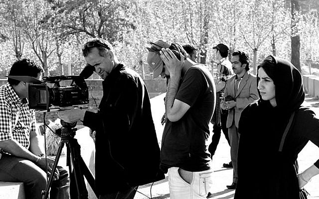 "In this undated photo provided by Iranian filmmaker Keywan Karimi, from second left to right, cameraman Arasto Givi, filmmaker Karimi and assistant director Fateme Hafezi work on a scene of a film titled ""Writing On The City,"" in Tehran, Iran. (Iranian filmmaker Keywan Karimi via AP)"
