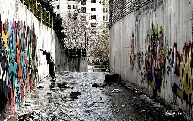 "In this undated photo provided by Iranian filmmaker Keywan Karimi, graffiti artist who goes by the name 'FRZ' paints a wall during a scene in the film titled ""Writing On The City,"" in Tehran, Iran. (Iranian filmmaker Keywan Karimi via AP)"