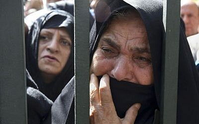 In this October 4, 2015, file photo, an Iranian mourner weeps during a funeral ceremony, attended by thousands of mourners in Tehran, Iran, for some of the pilgrims who were killed in a stampede during the hajj pilgrimage in Saudi Arabia in September 2015. (AP/Vahid Salemi, File)