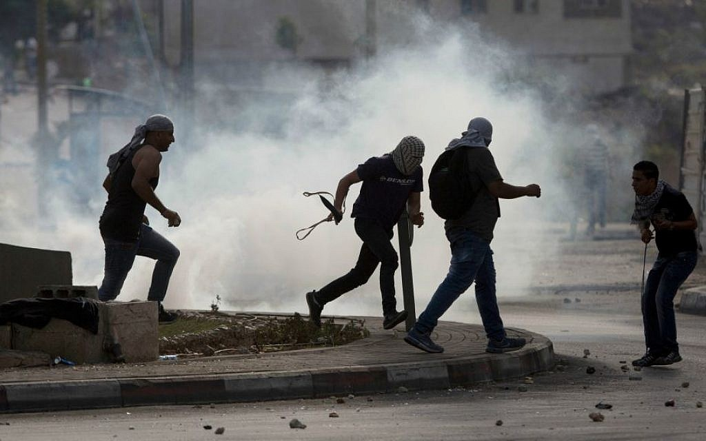Palestinians run from tear gas during clashes with Israeli troops near Ramallah, West Bank, Monday, Oct. 12, 2015. (AP Photo/Majdi Mohammed)