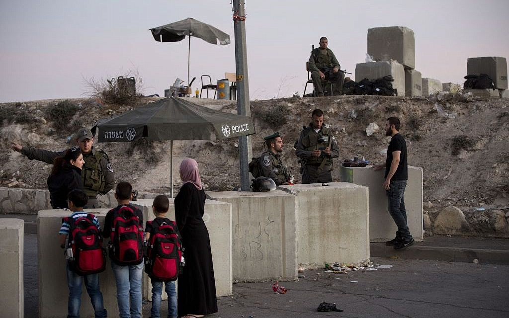 In this Thursday, Oct. 22, 2015 file photo, Israeli border police check Palestinians' ID cards at a checkpoint as they exit the Arab neighborhood of Issawiyeh in Jerusalem. (AP Photo/Oded Balilty)
