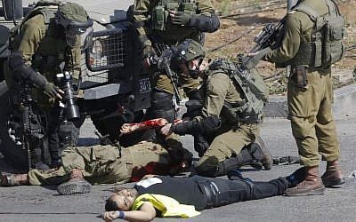 """Israeli soldiers treat a wounded comrade after he was stabbed by a Palestinian, seen on the ground, during clashes in Hebron, West Bank Friday, Oct. 16, 2015. The Palestinian man wearing a yellow """"press"""" vest and a T-shirt identifying him as journalist stabbed and wounded an Israeli soldier in the West Bank city of Hebron on Friday before being shot dead by troops, the latest in a month-long spate of attacks. (AP/Nasser Shiyoukhi)"""