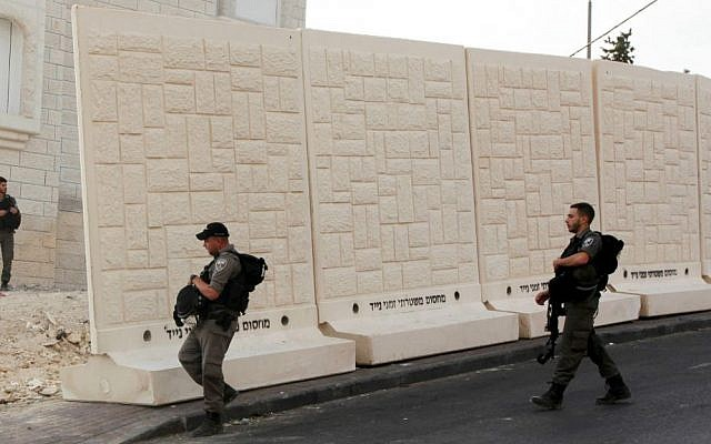 Israeli border policemen walk by the wall being built between Palestinian and Jewish neighborhoods in Jerusalem Sunday, Oct. 18, 2015. (AP Photo/Mahmoud Illean)