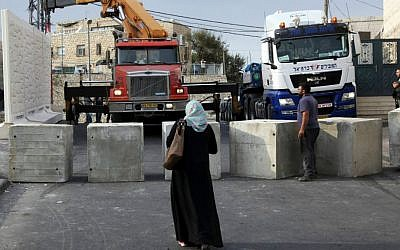 Palestinians watch a wall being built between Palestinian and Jewish neighborhoods in Jerusalem Sunday, Oct. 18, 2015. (AP Photo/Mahmoud Illean)