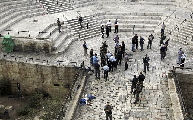 Israeli police stand near the body of a Palestinian who, according to the police, stabbed two police officers at the Damascus Gate of Jerusalem's Old City, Saturday, Oct. 10, 2015. (AP Photo/Mahmoud Illean)