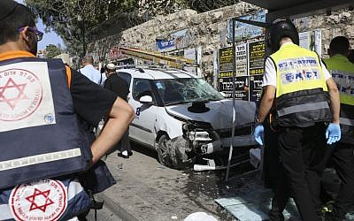 Police and emergency services respond to an attack in Jerusalem on October 13, 2015 after Palestinian rammed a vehicle into a bus stop then got out and started stabbing people. (AP/Oren Ziv)