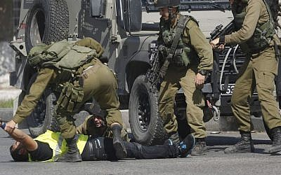"""An Israeli soldier grabs a Palestinian's hand holding a knife after he stabbed another Israeli soldier, seen on the ground during clashes in Hebron, West Bank on Friday, Oct. 16, 2015. The Palestinian man wearing a yellow """"press"""" vest and a T-shirt identifying him as journalist stabbed and wounded an Israeli soldier in Hebron on Friday before being shot dead by troops, the latest in a month-long spate of attacks. (AP/Nasser Shiyoukhi)"""