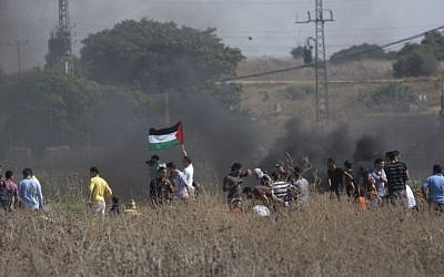 Palestinians gather during clashes with Israeli soldiers on the border near Gaza City, Friday, Oct. 9, 2015. (AP/Khalil Hamra)