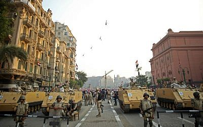 In this Sunday, Oct. 6, 2013, file photo, Egyptian military helicopters fly overhead as army soldiers stand guard at an entrance to Tahrir Square, in Cairo. (AP Photo/Khalil Hamra, File)