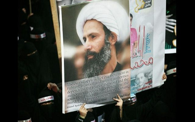 In this Sunday, Sept. 30, 2012 file photo, a Saudi anti-government protester carries a poster with the image of jailed Shiite cleric Sheik Nimr al-Nimr during the funeral of three Shiite Muslims allegedly killed by Saudi security forces in the eastern town of al-Awamiya, Saudi Arabia. (AP)