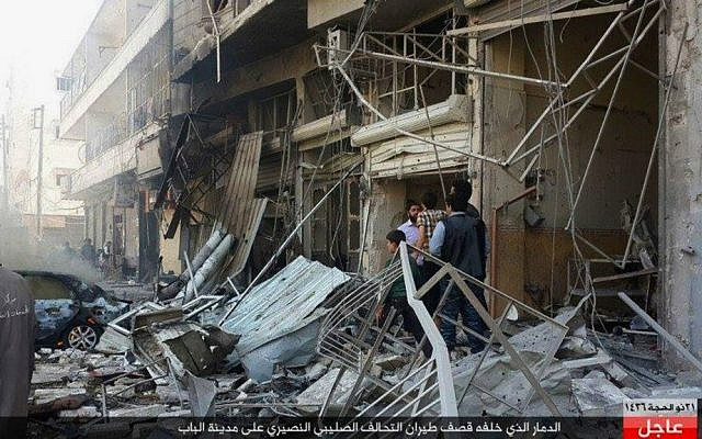 In this Monday, Oct. 5, 2015 photo released by the Rased News Network, a Facebook account affiliated with Islamic State, people gather at the site of an airstrike in Al-Bab on the outskirts of Aleppo, Syria. (Rased News Network via AP)