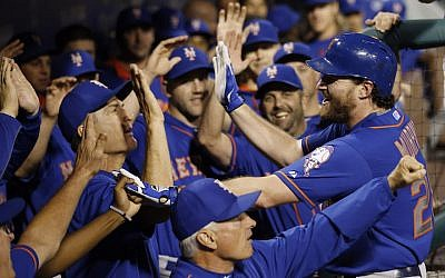 New York Mets' Daniel Murphy celebrates with teammates in the dugout after hitting a three-run home run off Philadelphia Phillies starting pitcher Alec Asher during the first inning of a baseball game, Wednesday, September 30, 2015, in Philadelphia (AP Photo/Matt Slocum)