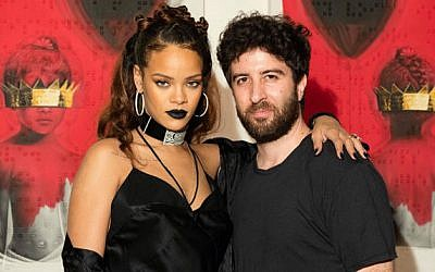 Pop star Rihanna and her Israeli-born muse, Roy Nachum pose in front of the art he created for her latest album (Courtesy Roy Nachum)
