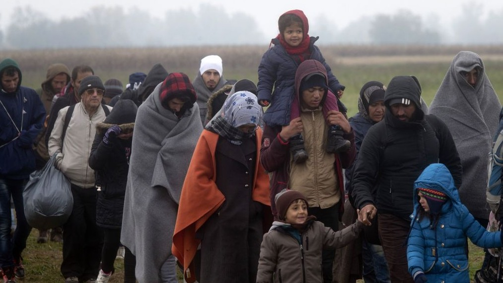 Migrants move through a field after crossing from Croatia, in Rigonce, Slovenia, Sunday, Oct. 25, 2015. (AP/Darko Bandic)