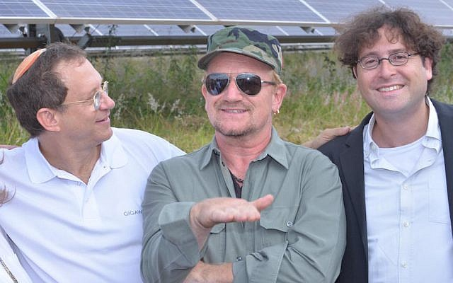 Gigawatt Global Co-Founders Yosef Abramowitz (L) and Chaim Motzen (R) with U2's lead singer Bono at Gigawatt Global's solar field in Rwanda (Courtesy)