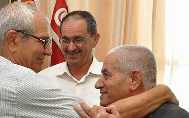 Houcine Abassi, secretary general of the Tunisian General Labor Union (UGTT), right, is congratulated by unidentified union members in his office at the headquarters in Tunis, Tunisia, Friday, Oct. 9, 2015. Abassi is one of the four members of the Tunisian National Dialogue Quartet to be awarded the 2015 Nobel Peace Prize on Friday by the Norwegian Nobel Committee. (AP Photo)