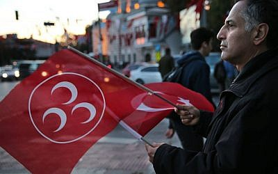 A supporter of Turkey's opposition Nationalist Action Party, (MHP), waves his party and nation flags, in Istanbul, Saturday, Oct. 31, 2015. (AP Photo/Hussein Malla)