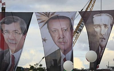 Banners (from left to right) of Turkish Prime Minister Ahmet Davutoglu, President Recep Tayyip Erdogan, and Turkish Republic founder Mustafa Kemal Ataturk, during a rally of supporters of Davutoglu in Istanbul, October 25, 2015. (AP/Lefteris Pitarakis, File)
