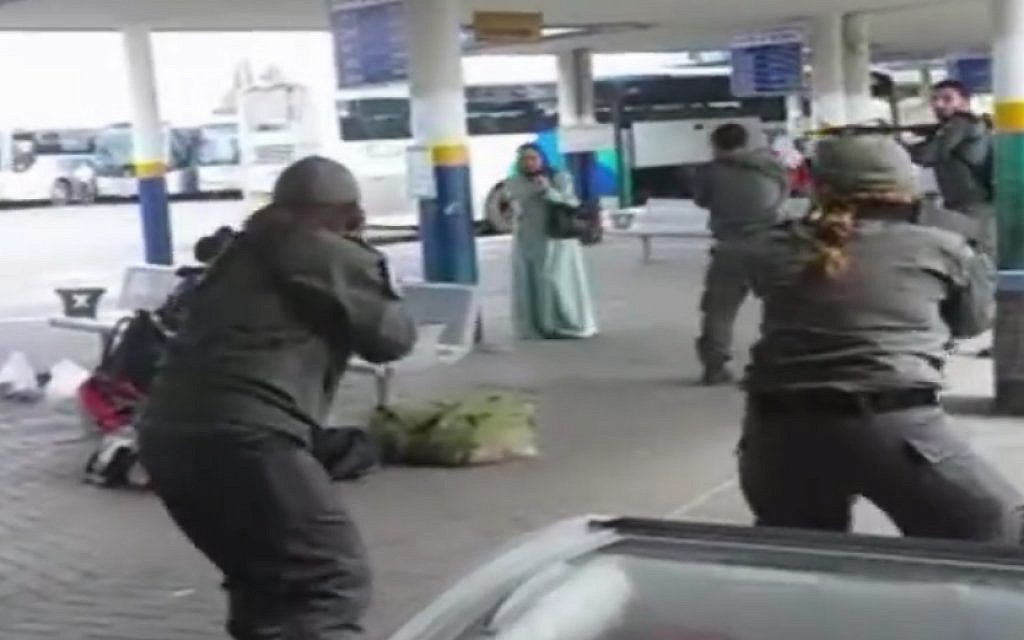 A still image taken from cellphone footage of security forces surrounding a knife-wielding Israeli Arab woman after she allegedly tried to stab a security guard at Afula bus station on Friday, October 9, 2015.  (screen capture)