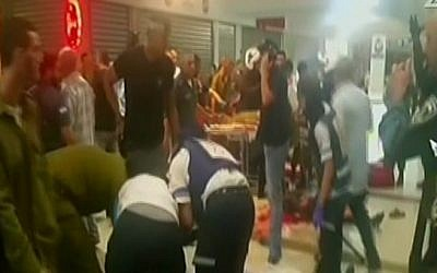 Paramedics treating victims after a terror attack at the Beersheba Central Bus Station on October 18, 2015. (screen capture: Channel 2)
