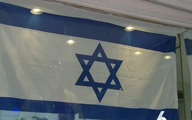 A Muslim family from Turkey hangs an Israeli flag outside its tailor shop to show support for Jewish state amid wave of violence in October 2015. (Screenshot/NBC Miami)