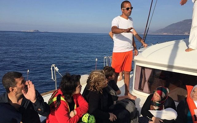 Refugees from Iraq and Syria after being rescued by members of an Israeli yacht crew off of the Greek coast on October 18, 2015. (Gal Baruch, courtesy)