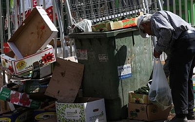 An elderly man searches among the garbage near the food market in the central Israeli city of Petah Tikva, June 24, 2015. (Nati Shohat/Flash90)