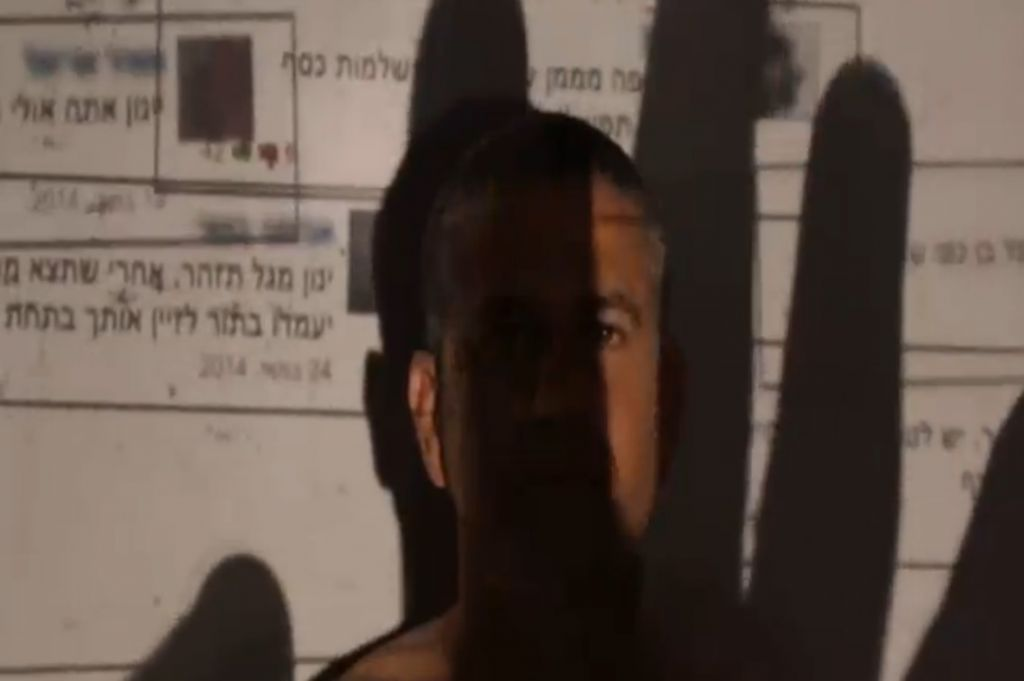 Jewish Home MK Yinon Magal, covered by the shadow of a hand placing comments written against him on Facebook, in a clip published by several MKs together to highlight the dangers of online incitement. (Screen capture Channel 2)