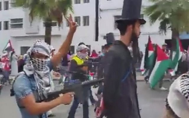 A still image from a video of a pro-Palestinian demonstration in Casablanca, Morocco, in which 'Jews' are held at gunpoint by keffiyeh-clad protesters, October 25, 2015. (screen capture: alyaexpress-news.com)