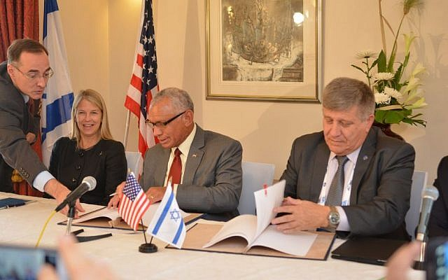 NASA Administrator Charles Bolden (center) and Israel Space Agency Director General Menachem Kidron (right) sign cooperation agreement at the International Astronautical Congress held in Jerusalem, October 13, 2015 (Photo by Yair Zrika)