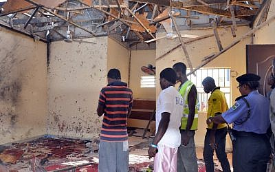 A picture taken on October 23, 2015 in Maiduguri, northeast Nigeria, shows people standing in a mosque following a suicide bombing. (AFP/STRINGER)