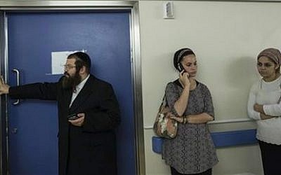 In this Monday, Oct. 12, 2015 photo, friends and relatives of Odel Bennett stand outside her room at the Hadassah Medical Center in Jerusalem (AP Photo/Tsafrir Abayov)