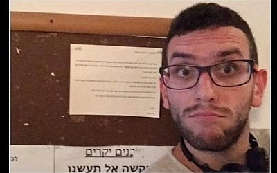 An Arab resident of Tel Aviv takes a selfie in front of an anti-Arab notice hung in his building's stairwell on October 12, 2015. (Screen shot: Facebook)