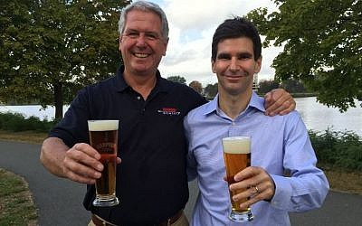 To craft its new Charles River Pale Ale beer, Boston's Harpoon Brewery partnered with Israeli-founded Desalitech to purify 300 gallons of the Charles River, appearing in the background of this September 2015 photo with Harpoon president Charlie Storey (left) and Desalitech CEO Nadav Efraty. (courtesy)