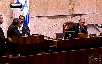 Immigration and Absorption Minister Ze'ev Elkin, left, surrounded by Knesset ushers, faces off with MK ands deputy speaker Ahmad Tibi, right, of the Joint (Arab) List during a heated exchange in the Knesset that ended with Elkin's removal from the plenum, October 21, 2015. (YouTube/99knesset)