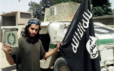 Abdelhamid Abaaoud, the suspected mastermind of the Paris terror attacks on November 13, 2015, waves an Islamic State flag in this undated picture taken from a magazine published by IS. (screenshot)
