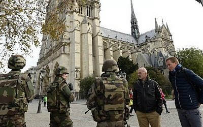 French soldiers patrol in front of Notre Dame de Paris Cathedral in Paris on November 14, 2015, following a series of coordinated attacks in and around Paris late Friday that left at least 128 people dead. (AFP PHOTO/BERTRAND GUAY)