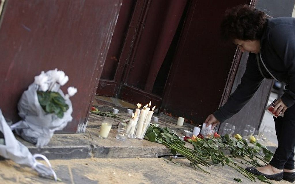A woman leaves candles and flowers outside of the Carillon bar in the 10th district of Paris on November 14, 2015, after a series of attacks in and around the city left at least 128 people dead. (AFP PHOTO/KENZO TRIBOUILLARD)