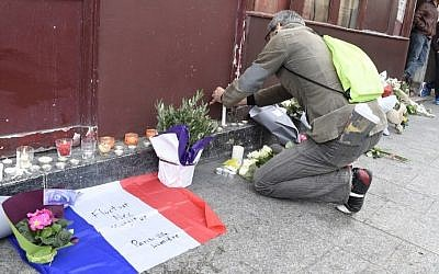 Flowers, candles and the French national flag with Paris's Latin motto 'Tossed but not sunk' written on it, are laid outside next to a Cambodian restaurant a day after 12 people were killed there, on November 14, 2015. (AFP PHOTO/DOMINIQUE FAGET)