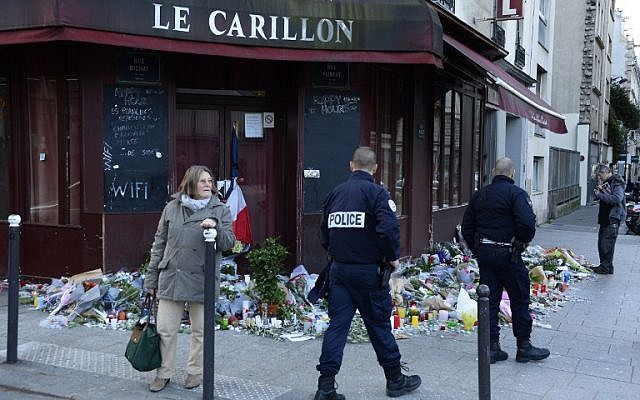Police officers walk past flowers, notes and candles at a memorial site outside the Carillon bar, in the 10th District of Paris, for victims of the November 13 terrorist attacks in Paris, November 15, 2015. (AFP/Bertrand Guay)