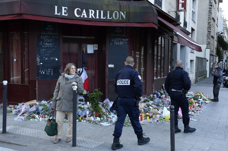 Police officers walk past flowers, notes and candles at a memorial site outside of the Carillon bar, in the 10th district of Paris, for victims of the November 13 terrorist attacks in Paris, November 15, 2015. (Photo by AFP Photo / Bertrand Guay)
